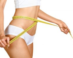 14852709 - woman measuring her waistline. perfect slim body. diet